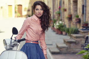 beautiful woman sitting on a italian scooter.